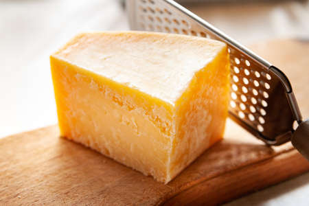 Cheese and grater. Piece of parmesan on a wooden board. Grater for grating cheese. Traditional food. 版權商用圖片