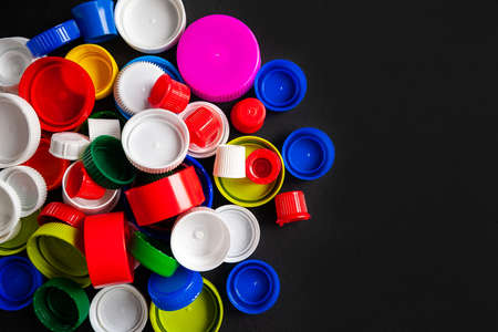 Top view of a pile of plastic bottle caps on a black background with copy space. Recycled plastic bottle caps. Separate garbage collection. Recycling of plastic for prosthetics. Selective focus. Multicolored texture.