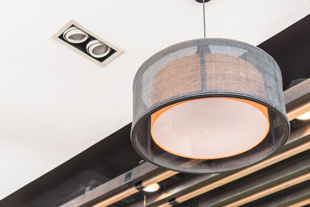 lampshades: The orange round stylish lampshades hang from ceiling Stock Photo