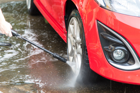 Car Wash Close up. Washing red modern car with high pressure water.