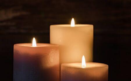 Three burning candle flames at night