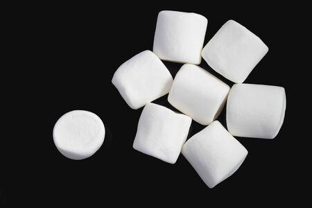 Group of white marshmallows on black background