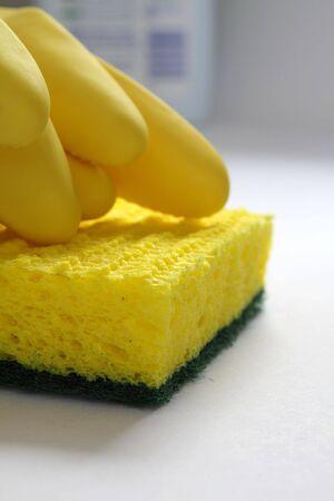 黄色いゴム手袋、台所のテーブルで黄色いスポンジ