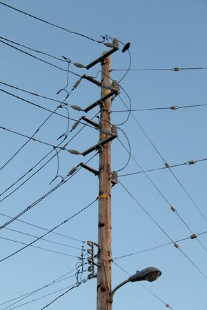 telegraphs: Telegraph pole with a lot of wires over blue sky Stock Photo