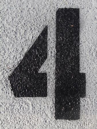 Black number four painted on the asphalt