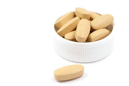 白い背景で隔離された白いプラスチック製のキャップでマルチ ビタミンの丸薬