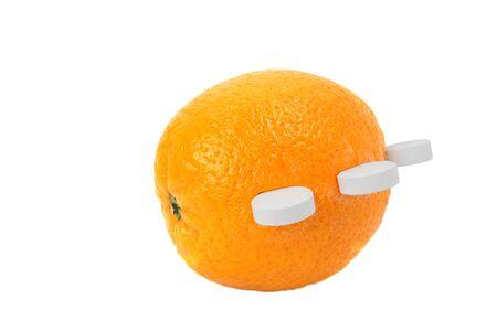 白い背景に分離されたビタミン C の白い丸い錠剤と熟したオレンジ色