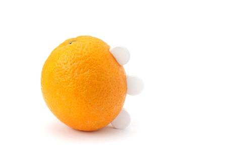 白い背景に分離されたビタミン C の 3 つの白い丸形錠と熟したオレンジ色