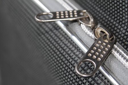clasps: Two zipper clasps on the grayish suitcase