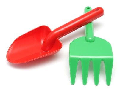 Toy red shovel and green rake isolated on white background