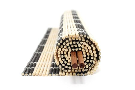 Rolled bamboo mat with a pair of chopsticks isolated on white background