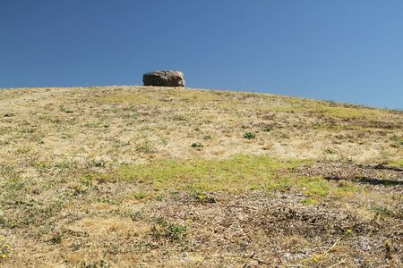 A rock on the hill on sunny day