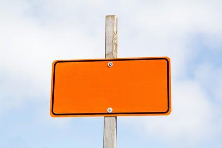 曇り空に明るいオレンジ道路標識 写真素材