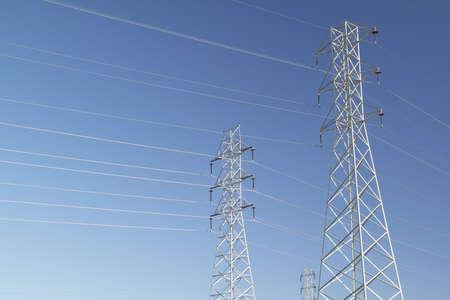 over voltage: High voltage power lines over blue sky