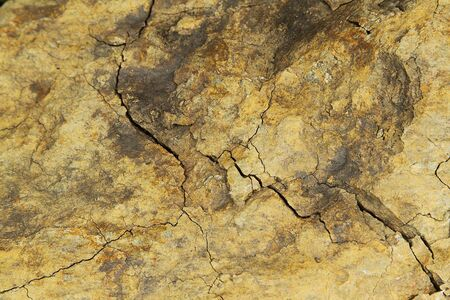 Old brown cracked rock close up photo