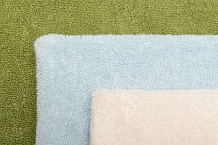 Closeup photo of three bath towels of different colors