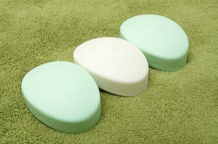 緑のバスタオルに石鹸の 3 つのバー
