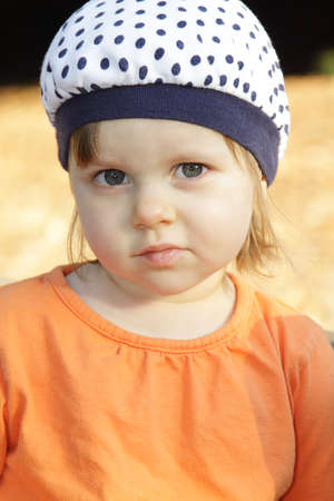 Cute little girl in orange shirt and white hat outdoors