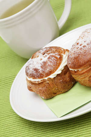 Two profiterole on a plate and a cup of green tea Stock Photo - 9133970