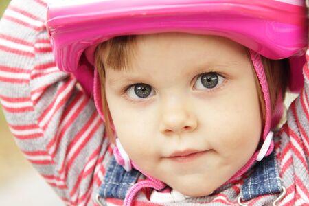 ピンクの自転車のヘルメットを持つ少女の肖像画 写真素材