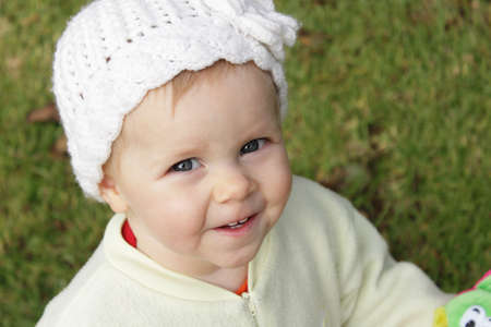 Cute infant girl with knit white hat Фото со стока