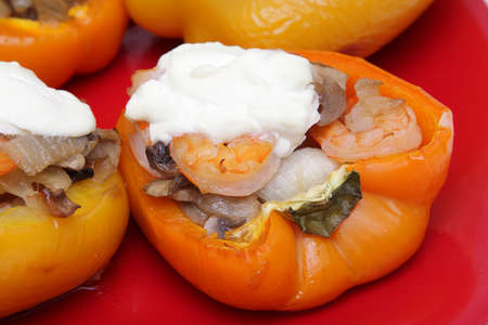 Stuffed pepper with shrimps, mushrooms and onion on red plate Stock Photo