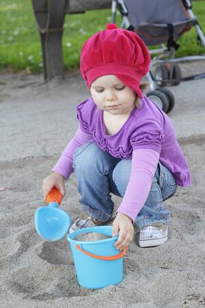 Little girl playing with sand on a playground