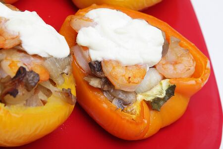 Peppers stuffed with shrimps, mushrooms and onion on red plate Stock Photo