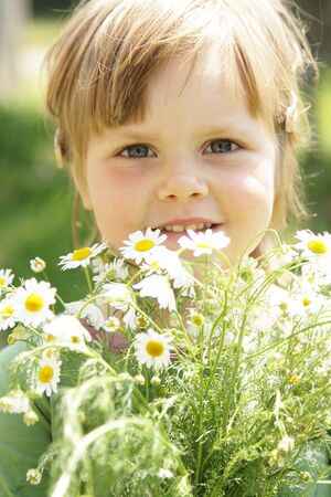 Little girl with daisies outdoor on sunny day
