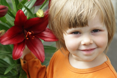 Little girl with a red lily in the garden