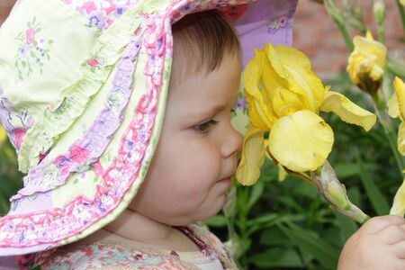 Cute little girl with yellow flower in the garden Stock Photo