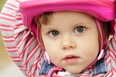 Cute little girl with a pink helmet Stock Photo
