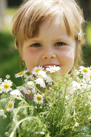 Cute little girl with white daisies outdoor Standard-Bild