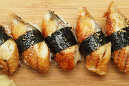 Group of broiled eel (unagi) sushi with sesame seeds