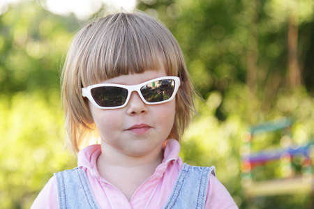 Cute little girl with sunglasses in the garden