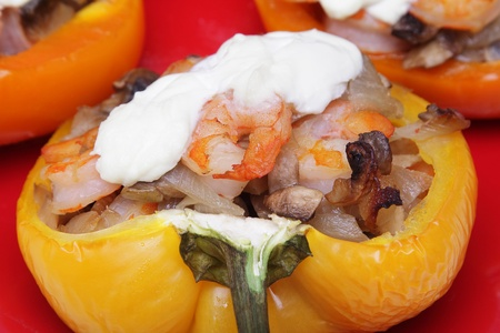 Pepper filled with shrimps and onion on red plate