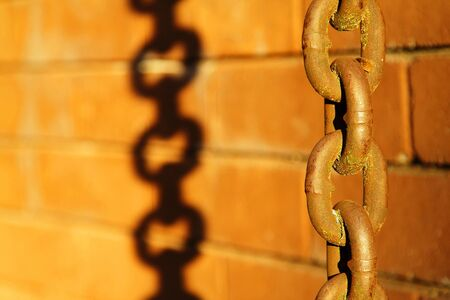 Old rusted chain and its shadow on a brick wall Stock Photo