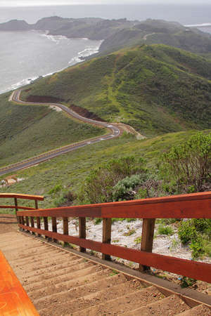 Wooden staircase to observation point with hills by ocean on background
