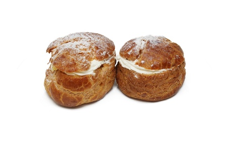 Two pastries filled with custard over white background