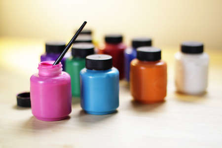 Group of paints in bottles with a small brush, shallow depth of field