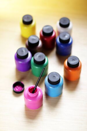 Group of paints bottles of various colors on a table, view from above Stock Photo