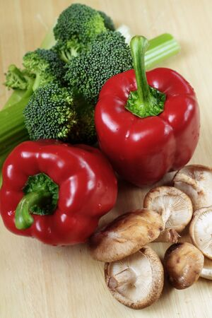 Vegetables on kitchen table: red peppers, broccoli, celery and shiitake mushrooms