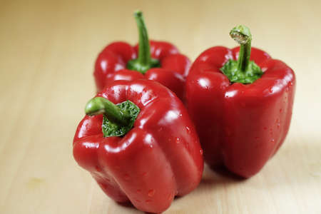Three red peppers on a kitchen table