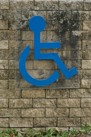 Blue sign of a handicap accessible sign on a brick wall photo