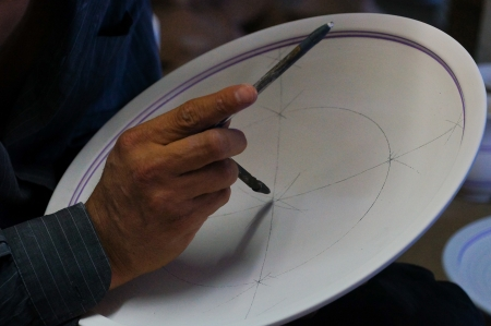 A ceramic artist draws a design on a plate in Fez, Morocco   Fez has been a center of fine pottery production for thousands of years