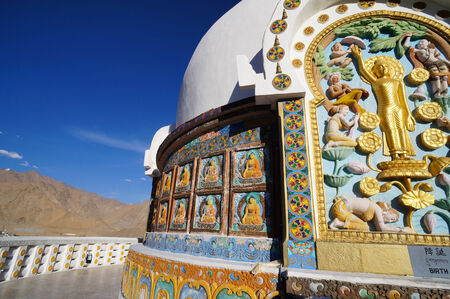 colorful paintings on the wall of buddhist stupa with himalayas in the background, stylized and filtered to look like an oil painting. Location: Shanti Stupa, Leh, Ladakh, India. Stock Photo