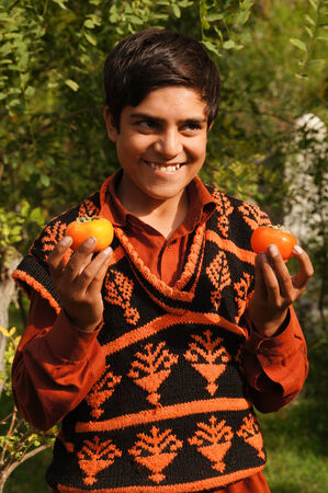 pakistani pakistan: Pakistani boy showing persimmons at his fathers shop in Pakistan Editorial