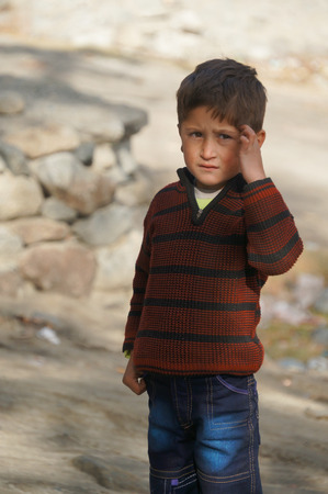 pakistani pakistan: A cute Pakistani boy wondering about something in Northern Pakistan Editorial