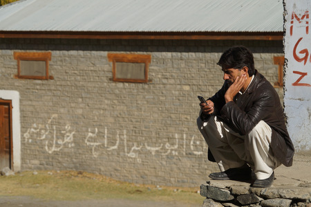 pakistani pakistan: A Pakistani man looking at his cellphone,Northern Pakistan