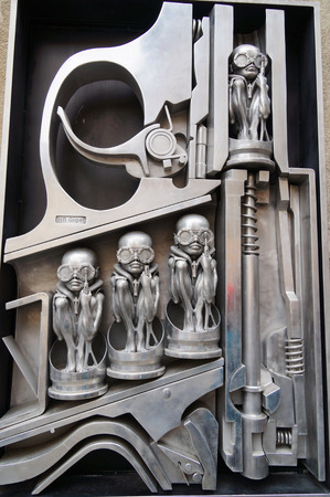 surrealist: Birth machine sculpture depicting a crosscut of a gun shooting alien figurines In front of H.R. Giger Museum,Gruyeres,Switzerland